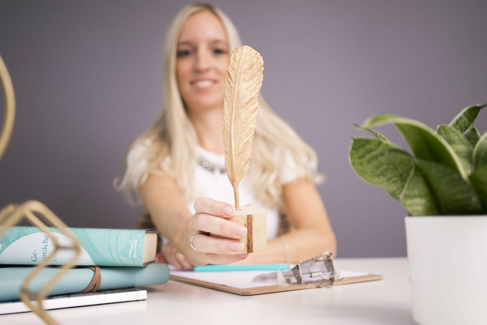 Frau mit Schreibfeder in der Hand